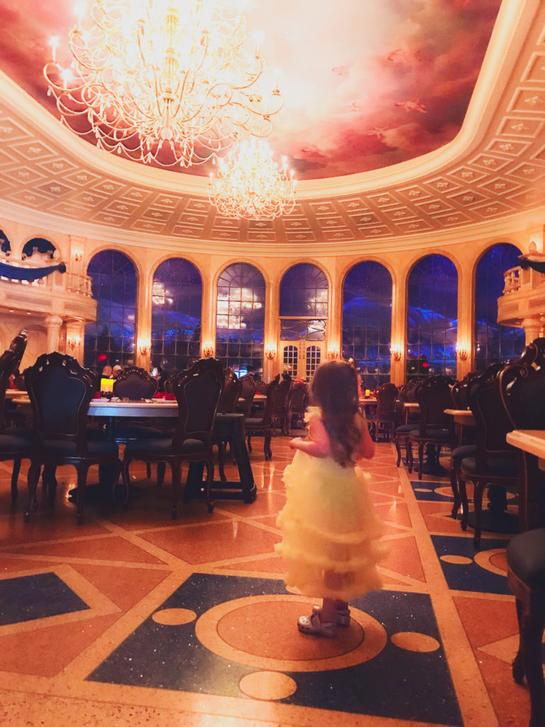 The Main Ballroom at Be our Guest restaurant. It snows outside the windows.