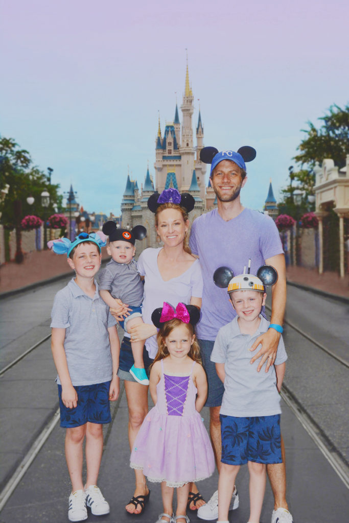 family in front of cinderella's castle on main street